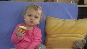 Attractive young girl taking bite from big red apple at home. stock footage