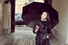 Attractive young girl with ubrella in an old town Stock Photography