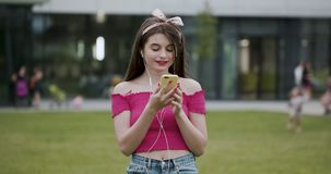 Attractive young girl in urban city streets background listening to music with headphones. Woman wearing pink blouse and. Portrait of young cute attractive young stock video