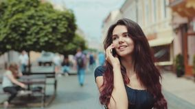 Attractive young girl walks down the crowded city street, picks up the phone, happily talks. Shops, passersby, urban. Buildings on the background. Playful mood stock footage