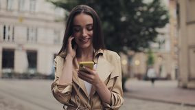 Attractive Young Girl Wearing Headphones Listening to Music Looking into her Smartphone and Smiling Standing at City. Background stock footage
