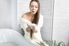 Attractive young girl in a white bathrobe applies cream to the skin while sitting in the interior of the bathroom and. Doing morning procedures. Skin and body royalty free stock photo
