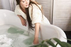 Attractive young girl in a white bathrobe applies cream to the skin while sitting in the interior of the bathroom and. Doing morning procedures. Skin and body royalty free stock image