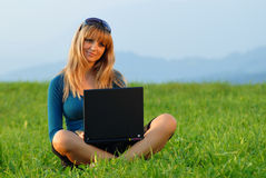 Attractive young girl working on computer in nature Royalty Free Stock Photos