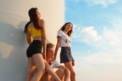 Teenagers sitting near a windmill on a blue sky background. Two hot girls and a handsome guy. Youth concept. Copy space. stock images