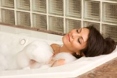 Attractive young gorges female taking bubble bath. Bathroom : Sensual sexy woman relaxing in a bathtub foam with closed eyes Royalty Free Stock Photos