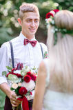 Attractive young groom in blue braces stands before bride royalty free stock photos