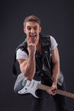 Attractive young guitarist is making his Stock Photography