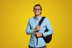 Attractive young guy in blue shirt and eyeglasses holding backpack and smiling at camera on yellow backdrop royalty free stock image