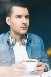 Attractive young guy is drinking hot beverage Royalty Free Stock Image