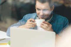 Attractive young guy is enjoying hot beverage Royalty Free Stock Photography