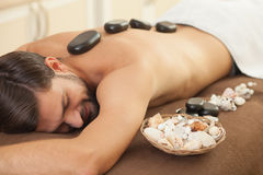 Attractive young guy is getting back massage royalty free stock photos