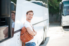 Attractive young guy is ready for his journey. Handsome man is standing near a bus and leaning on it. He is holding a rucksack and smiling. The man is looking at Royalty Free Stock Photos