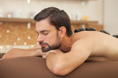 Attractive young guy is relaxing at beauty salon Stock Photos