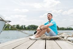 Attractive young guy sits in blue polo on pier near the yacht. smiled tourist handsome man relaxing and enjoying the view on pier. In marina on sky and tree Royalty Free Stock Photo