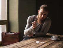 Attractive young guy is solving a problem. Look at this puzzle. Portrait of bearded man holding a puzzle in his hand. He is sitting at the table and looking Royalty Free Stock Photos