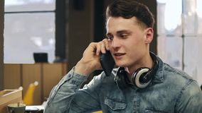 Attractive young guy is talking to someone on the cell phone. Indoors footage. Attractive young guy is talking to someone on the cell phone. Indoors footage stock footage