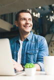 Attractive young guy is working on computer Royalty Free Stock Photos