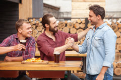Attractive young guys are greeting in beerhouse Stock Photos