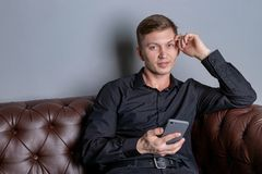 Attractive young handsome man wearing black shirt sitting on the leather sofa holding smartphone. Comfort and relaxation royalty free stock image