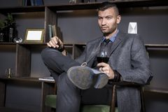 Attractive young handsome stylish man in suit sits in chair with glass of red wine. Fashionable elegant man in luxurious interior royalty free stock image