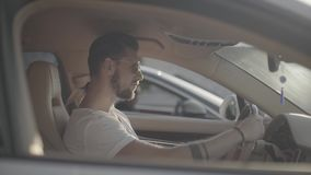 Attractive young handsome tattooed man in sunglasses sitting in luxury sport racing car opposite to rival ready to start. A car race on empty highway road stock footage