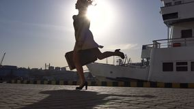 Attractive young happy blonde woman in trench with vintage suitcase walking and jumping on the jacht pier. Slow Motion stock video