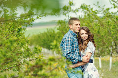 Attractive young happy couple on a spring garden Royalty Free Stock Photos