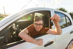 Attractive young happy man showing his new car keys and laughing Royalty Free Stock Photos