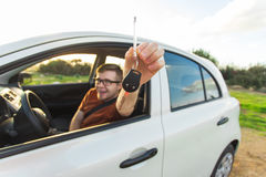 Attractive young happy man showing his new car keys and laughing Royalty Free Stock Photography