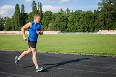 Attractive young healthy male runner is training. Handsome sportsman is running towards track in stadium. He is looking forward with concentration. There is copy Royalty Free Stock Image