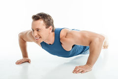 Attractive young healthy sportsman is doing push Royalty Free Stock Photo