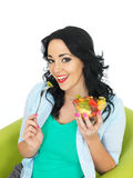 Attractive Young Heathy Woman Holding Up A Fresh Exotic Fruit Salad. Healthy attractive young woman, with dark wavy hair, and hispanic features, hold up a fresh Royalty Free Stock Image