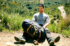 Attractive young hiker with rucksack resting on a halt on a mountain trail and looking away. Young hiker on the mountains, traveling, extreme stock photography