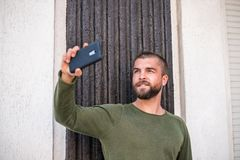 Attractive young hipster guy is making selfie. stock photo