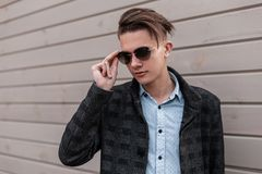 Attractive young hipster man with trendy hairstyle in stylish sunglasses in a vintage plaid jacket in shirt poses on the street. Near a wooden wall. Cute guy stock photo