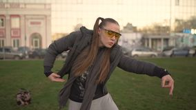 Attractive young hipster woman in a stylish look dancing freestyle on urban background at sunset or dusk. Attractive young hipster woman in a stylish look stock footage