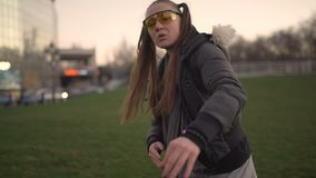 Attractive young hipster woman in a stylish look dancing freestyle on urban background at sunset or dusk. Attractive young hipster woman in a stylish look stock video footage
