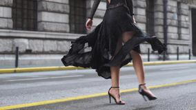 Attractive young woman in wonderful dress are walking on the street. Attractive young hispanic woman in wonderful black dress are walking on the street. red lips stock video