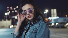 Attractive young hot brunette girl in jeans jacket and stylish sunglasses poses by the camera. Seductive look, stylish stock footage