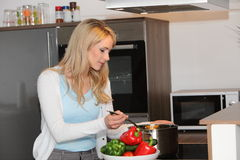 Attractive young housewife cooking in the kitchen royalty free stock photo