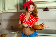 Attractive young housewife with curly hair in pinup style posing Stock Photos