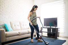 Musical young woman enjoying music on headphones and cleaning ca. Attractive young housewife using vacuum cleaner and listening to music on headphones in living Royalty Free Stock Image