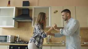 Attractive young joyful couple have fun dancing while cooking in the kitchen at home stock video footage