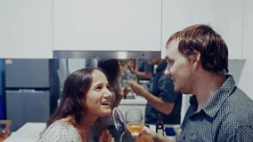 Attractive young joyful couple have fun dancing and singing with ladle drinks wine while cooking in the kitchen at home stock video