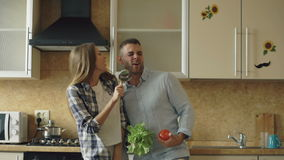 Attractive young joyful couple have fun dancing and singing while cooking in the kitchen at home stock footage