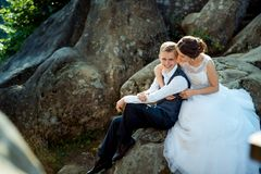 Attractive young just married are tenderly hugging while sitting on the rock. Attractive young just married are tenderly hugging while sitting on the rock Stock Images