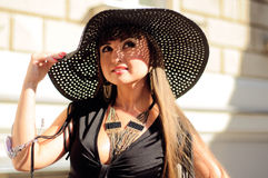 Attractive young lady in a black hat Royalty Free Stock Photos