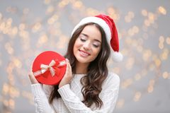 Attractive young lady in Christmas hat holding gift box. On blurred background Stock Photography