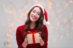 Attractive young lady in Christmas hat holding gift box. On blurred background Stock Photos